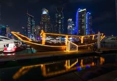 迪拜小游艇船坞城市光在与著名地标和游船的晚上打开了 免版税库存图片