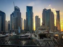 迪拜小游艇船坞小船口岸和塔在日落 免版税图库摄影