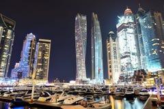 迪拜小游艇船坞的夜照明和Cayan耸立 免版税库存照片