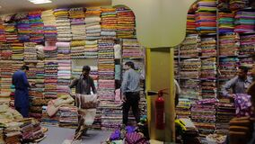 迪拜,阿拉伯联合酋长国- 2018年1月12日:卖主地毯和织品在地方市场上在世界村迪拜市 阿拉伯织品 影视素材