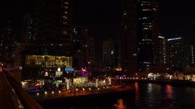 迪拜,阿拉伯联合酋长国- 2018年1月18日:夜城市在有现代摩天大楼和餐馆的走的街道上点燃在迪拜 股票视频