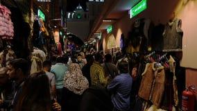 迪拜,阿拉伯联合酋长国- 2018年1月12日:在迪拜市阿拉伯联合酋长国拥挤地方市场鞋类、衣物、织品和地毯的人 股票录像