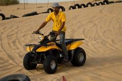 迪拜,阿拉伯联合酋长国- 2012年4月20日:徒步旅行队乘坐ATV的阵营职员所有地形车 库存图片