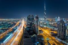 迪拜,阿拉伯联合酋长国- 2015年12月17日:迪拜的街市建筑学鸟瞰图在夜与和Burj哈利法里 免版税库存图片