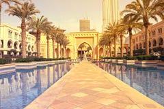 迪拜,阿拉伯联合酋长国- 2017年7月11日:Souk Al Bahar和绿松石湖周围的Burj哈利法看法由绿叶 图库摄影