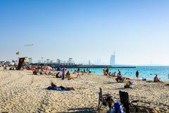 迪拜,阿联酋, 2018年4月20日:风筝海滩在有许多访客的迪拜和Burj Al阿拉伯旅馆在背景中 免版税库存照片
