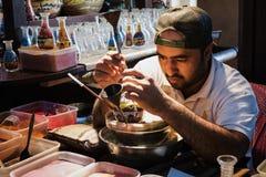 迪拜,阿联酋- 2016年12月7日:使用色的沙子,工匠做在瓶的纪念品 免版税库存照片