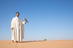 迪拜,阿联酋- 2016年12月2日 在猎鹰训练术训练期间的一只猎鹰在捉住诱剂的沙漠 库存照片