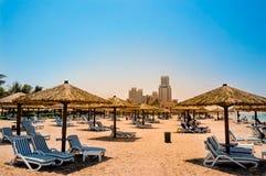 迪拜 天堂般的绿洲在Ras Al Khaimah 与sunbeds和遮光罩的海滩在迪拜,阿拉伯海湾的岸的 定调子 库存照片