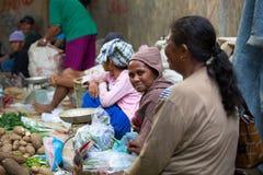 迪雅克人夫人在沙马林达本机市场上的卖食物 库存照片