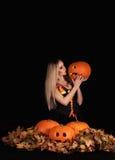 迷人的万圣夜巫婆用滑稽的南瓜 免版税图库摄影