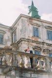 迷人的亲吻在与楼梯栏杆的老大阳台的新婚佳偶新娘和新郎在美丽的被破坏的巴洛克式的宫殿附近 免版税库存照片