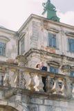 迷人的亲吻在美丽的被破坏的巴洛克式的宫殿附近的新婚佳偶新娘和新郎 免版税库存照片