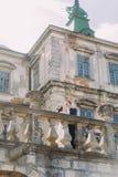 迷人的亲吻在老大阳台的新婚佳偶新娘和新郎在美丽的被破坏的巴洛克式的宫殿附近 库存照片