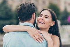 迷人的俏丽的青年千福年的拥抱接近的照片有乐趣周末春天散步时间享用穿戴蓝色 免版税库存照片