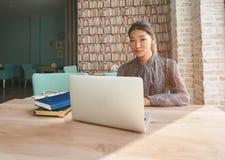 年轻迷人的在便携式计算机上的妇女观看的录影,当放松在咖啡馆在咖啡休息期间时, 免版税库存照片