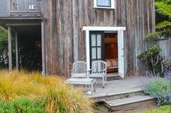 迷人的场面-两风化了在门廊的木椅子在门户开放主义之外到卧室在植物包围的土气房子里 免版税库存照片