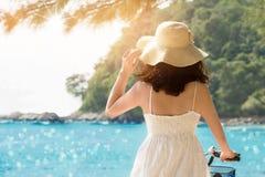 迷人的夫人拿着自行车的享用蓝色海和太阳发出光线 免版税库存图片