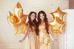 迷人的夫人集会,时尚金黄礼服的两名妇女与 库存照片