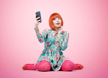 迷人的女孩与一个巧妙的电话坐背景 免版税库存照片
