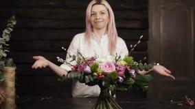 迷人的女孩卖花人在长的稳定的词根上提出她的工作,把桌放五颜六色的花美丽的花束  股票视频