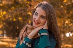 年轻迷人的女孩在公园在人看起来附近保持手去并且微笑 库存图片