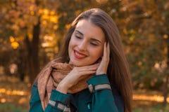 迷人的女孩在公园在面孔附近保留手结束了她眼睛和微笑 免版税库存图片