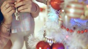 迷人的女孩垂悬在圣诞树的一个星与母亲 免版税库存照片