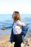 迷人的女孩沿海岸在沙子走和快活无所事事  免版税库存图片
