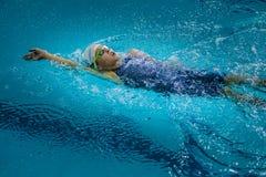 年轻迷人的女孩游泳仰泳 免版税库存图片