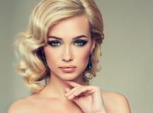 迷人的女孩白肤金发的卷发 免版税库存图片
