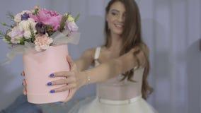 迷人的女孩给花花束在照相机的 影视素材