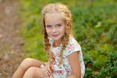 迷人的女孩画象有白肤金发的猪尾的,在草 库存图片