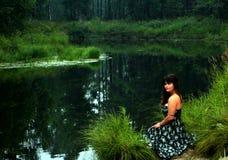 迷人的妇女坐河海岸在森林里 免版税库存图片