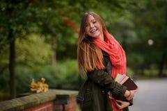 迷人的学生在一个美丽的秋天公园 免版税库存图片