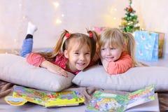 迷人的小女孩一起使用并且聊天,说谎在地板上和 免版税库存图片