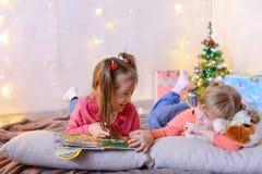迷人的小女孩一起使用并且聊天,说谎在地板上和 库存照片