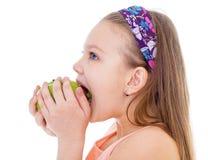 迷人的小女孩用绿色苹果。 免版税库存图片