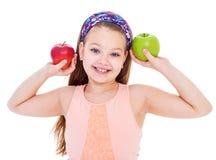 迷人的小女孩用绿色苹果。 免版税库存照片
