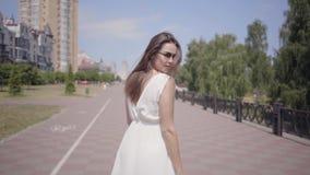 迷人的少女佩带的太阳镜和走一件长的白色夏天时尚的礼服户外 休闲俏丽 影视素材