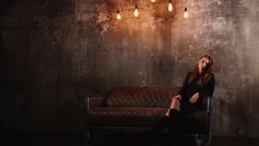 迷人的少妇在一个长沙发安置在黑暗的空的室 影视素材