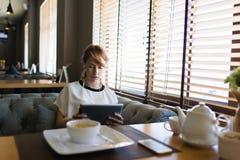 迷人的少妇有录影交谈,当早餐在咖啡店时 免版税图库摄影