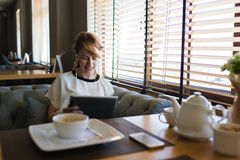 迷人的少妇有录影交谈,当早餐在咖啡店时 库存图片