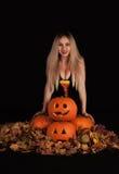 迷人的巫婆用滑稽的南瓜和叶子 免版税库存图片