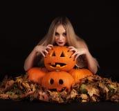 迷人的巫婆用滑稽的南瓜和叶子 图库摄影