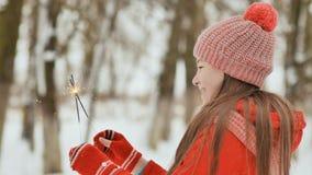 迷人的年轻女小学生快乐在她的手上拿着有一件礼物的一个被包装的箱子在冬天森林里 免版税库存照片