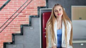 迷人的微笑的年轻偶然女孩画象有长的美丽的金发中景的 股票录像