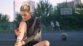 迷人的愉快的女性蓝球运动员佩带的耳机和键入在电话,坐地面,使用的人  股票录像