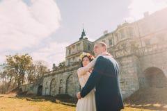 迷人的拥抱在美丽的被破坏的巴洛克式的宫殿附近的新婚佳偶新娘和新郎 库存照片