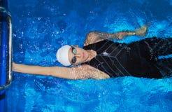 迷人的教练在水池游泳 免版税库存照片